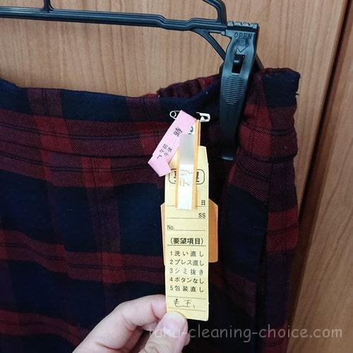 クリーニング東京へクリーニングに出したチェックのパンツ(赤)のタグ